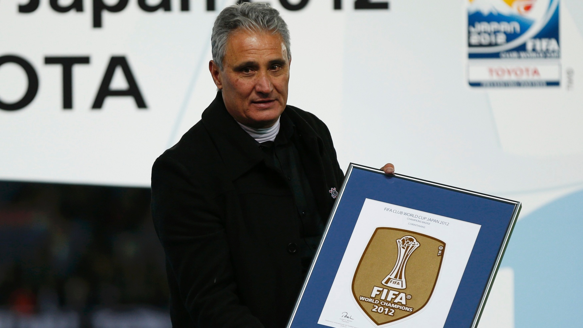 16.dez.2012 - Técnico Tite mostra o escudo de campeão mundial que será usado pelo Corinthians em seu uniforme durante o ano de 2013