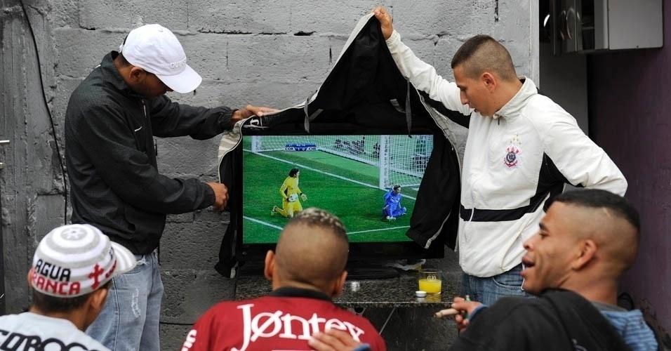 Aos 40min do segundo tempo, garoa forte começou a cair em Itaquera: solução foi colocar uma jaqueta sobre a tv a céu aberto