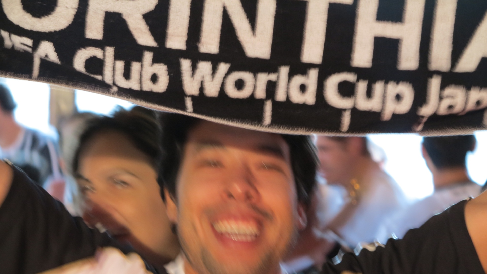 Torcedor mostra faixa de campeão mundial no bar Buddies, no Itaim, antes do apito final do árbitro