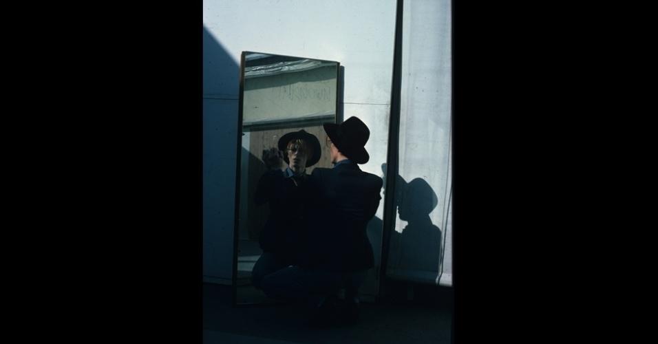 17.dez.2012 - O músico David Bowie é fotografado por Steve Shapiro enquanto olha no espelho. A imagem faz parte do livro