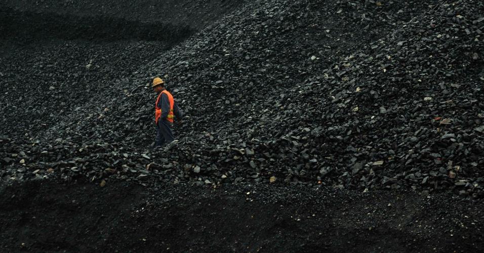 18.dez.2012 - Trabalhador anda entre as pilhas de carvão de uma carvoaria na China. Segundo relatório da gência Internacional de Energia, o carvão será primeira fonte de energia mundial em dez anos, superando o petróleo, devido ao desenvolvimento acelerado dos países emergentes, como China e Brasil
