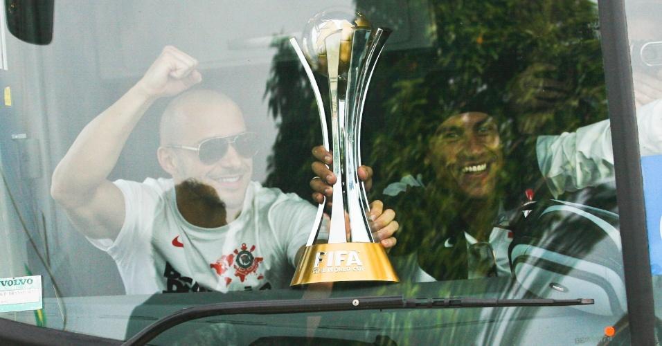 18.dez.2012- Ao lado de Paulinho e com a taça em mãos, Alessandro acena para torcedores que foram ao aeroporto de Guarulhos recepcionar a equipe corintiana