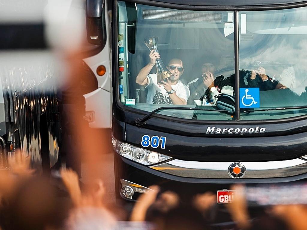 18.dez.2012- Dentro do ônibus, capitão Alessandro levanta a taça de Campeão Mundial aos torcedores que foram ao aeroporto de Guarulhos recepcionar a equipe corintiana