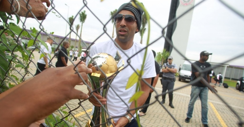 18.dez.2012- Emerson Sheik levou o troféu de campeão mundial até os torcedores corintianos no alambrado do CT Joaquim Grava