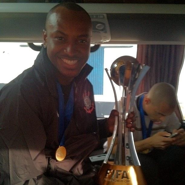 18.dez.2012- No ônibus com os jogadores do Corinthians na saída do aeroporto, cantor Thiaguinho posa com medalha e troféu de campeão mundial