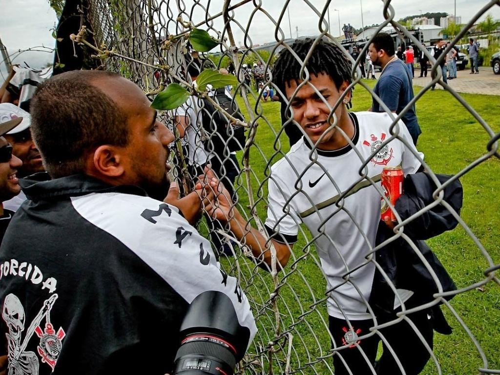 18.dez.2012- Pelas grades do CT Joaquim Grava, Romarinho cumprimenta torcedores corintianos