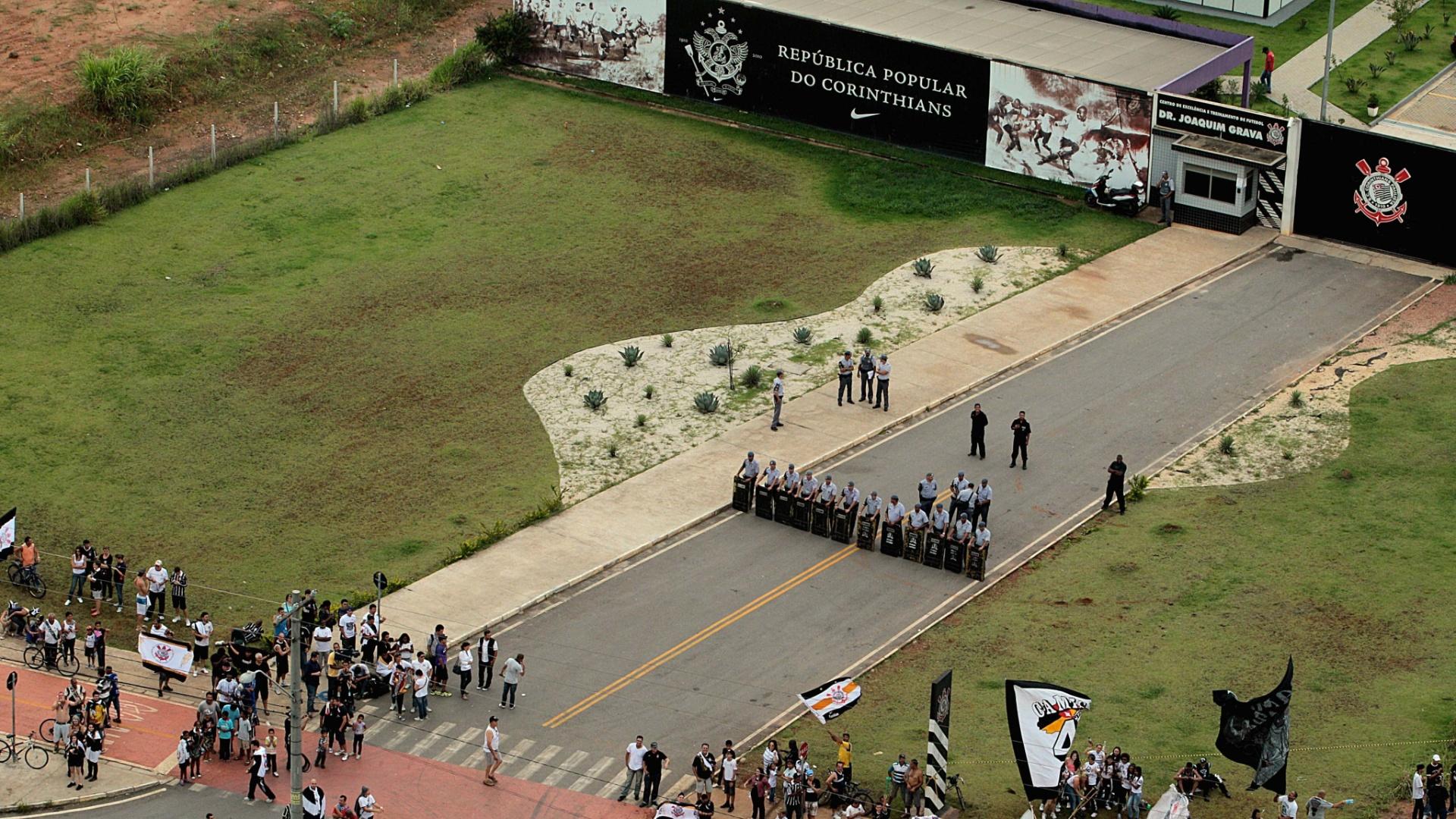 18.dez.2012- Policiais fazem barreira na entrada do CT Joaquim Grava na espera dos jogadores campeões mundiais