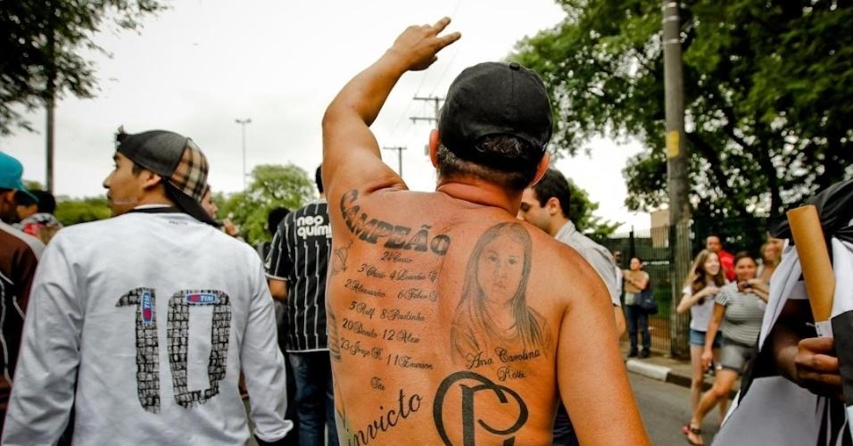 18.dez.2012- Torcedor exibe costas tatuadas com referência ao título da Libertadores do Corinthians em festa de comemoração do título mundial