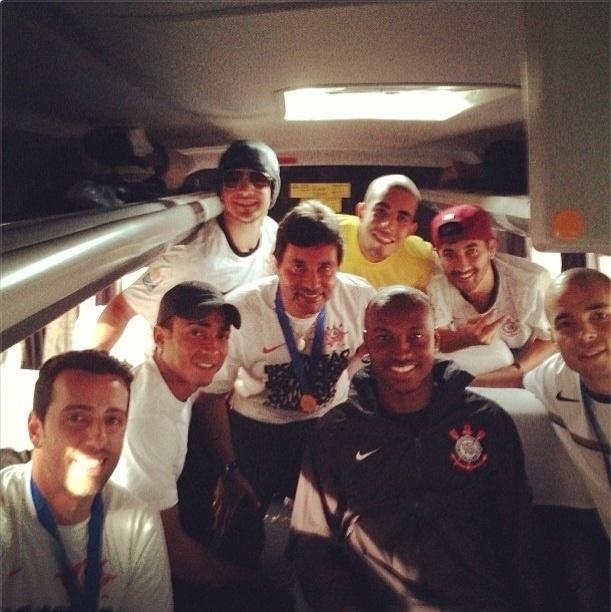 18.dez.2012-Jogadores do Corinthians tiram foto ao lado do cantor Thiaguinho em ônibus após desembarque em São Paulo