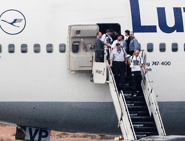 Jogadores corintianos desembarcam em São Paulo. Alessandro, o capitão, leva a taça na mão