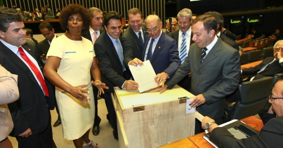 19.dez.2012 - Parlamentares testam na Câmara dos Deputados a urna especial construída para receber os votos de 463 páginas sobre a análise em bloco da derrubada dos vetos da presidente Dilma Rousseff (PT) ao projeto de redistribuição do royalties do petróleo e a outros 3.000 projetos de lei