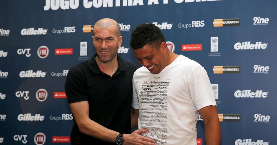 19.dez.2012 - Zidane brinca com a boa forma de Ronaldo após a entrevista coletiva realizada para divulgação do Jogo Contra a Pobreza, que será realizado na Arena do Grêmio, em Porto Alegre
