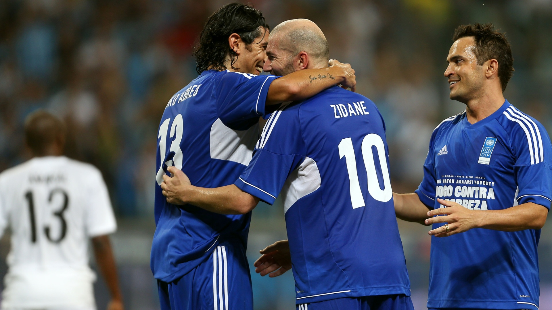 19.dez.2012 - Zidane comemora com Loco Abreu e Falco aps marcar no Jogo Contra a Pobreza