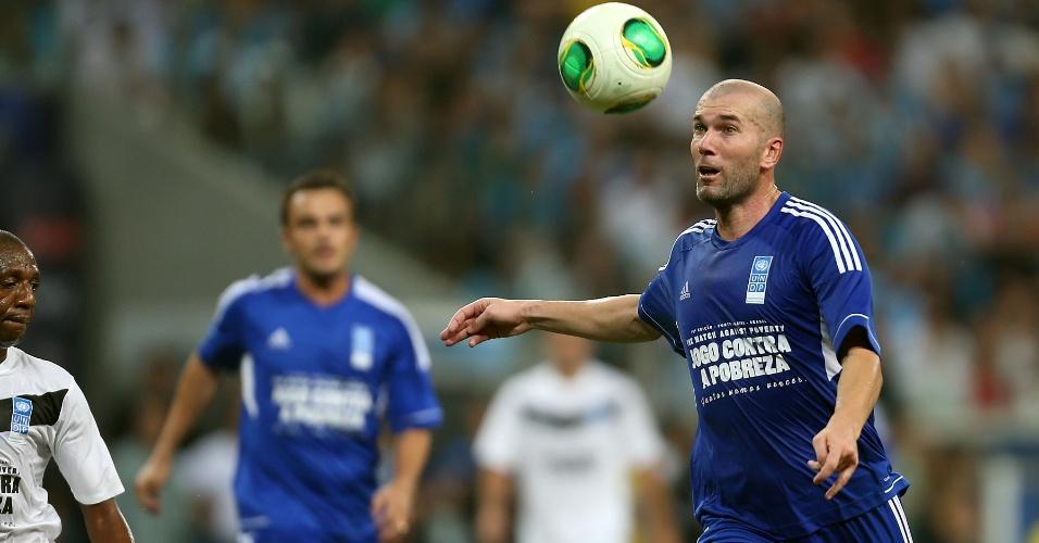19.dez.2012 - Zidane olha fixamente para a bola durante o Jogo Contra a Pobreza