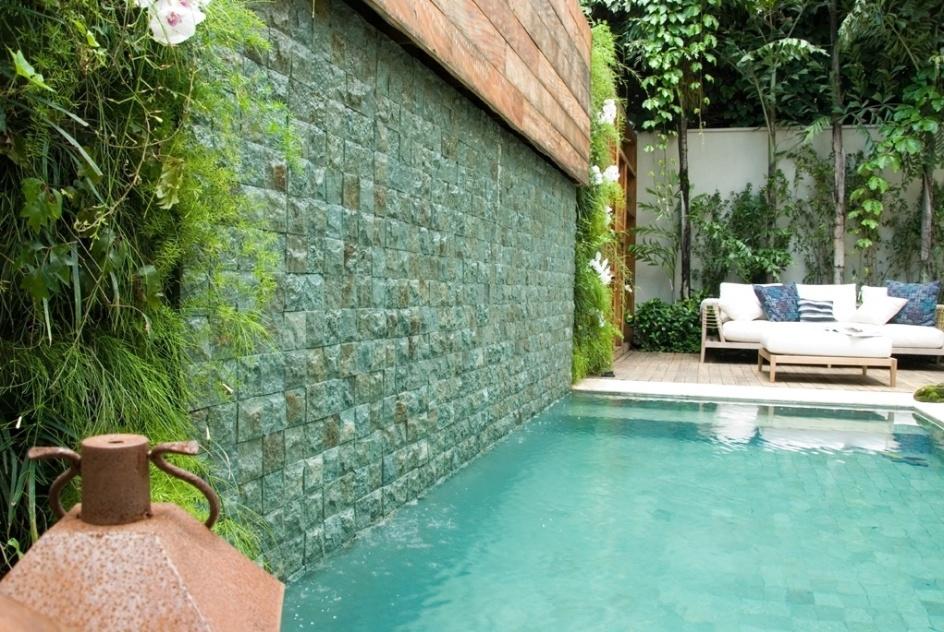Nessa residência em São Paulo (SP), a cascata que deságua na piscina de borda infinita cai de um painel de madeira e escorre por uma parede revestida com pedras asiáticas azuladas. Ladeando a cascata foram inseridos dois jardins verticais. O projeto é da paisagista Gigi Botelho