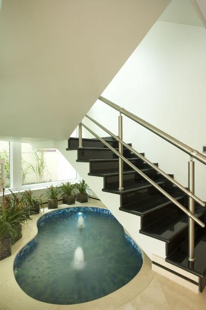 Para trazer um pouco da natureza para dentro do imóvel, o arquiteto Aquiles Kílaris aproveitou o espaço ocioso embaixo de uma escada para inserir um espelho d'água com formas orgânicas e dois jatos d'água espumosos
