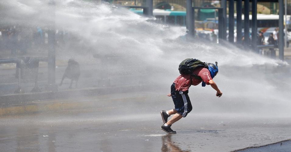 21.dez.2012 - Estudante é atingido por jato d'água durante protesto no Chile; manifestação não teria sido autorizada pelo governo
