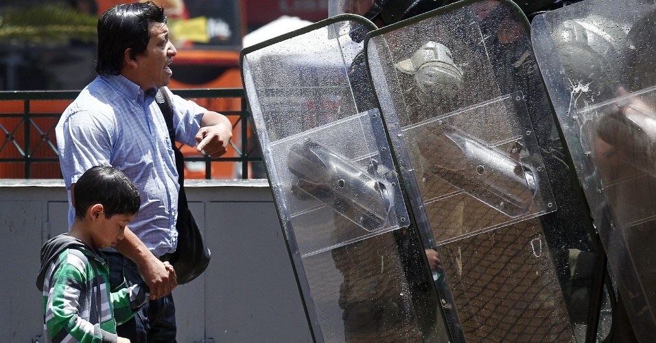 21.dez.2012 - Pai reclama com policiais após seu filho ser atingido por um jato d'água durante protesto de estudantes no Chile; movimento pede reforma educacional no país desde 2011