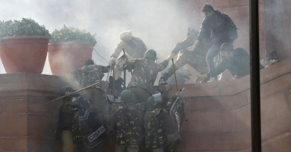 Policiais sobem em muro enquanto são enxotados por manifestantes perto do palácio presidencial em Nova Déli