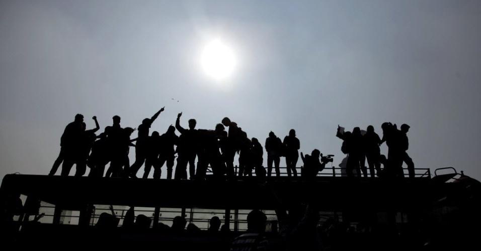 Manifestantes sobem em ônibus da polícia durante protestos após o estupro de uma estudante de 23 anos, em Nova Déli