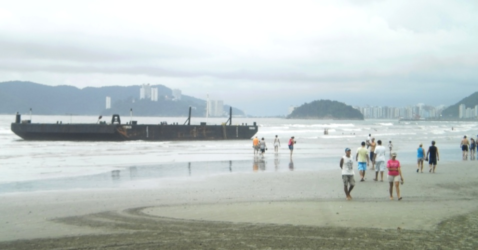 """23.dez.2012 - Balsa """"Rubineia"""", que encalhou por volta das 22h deste sábado (22) na praia do Boqueirão, em Santos (SP). A 300 metros dali, na praia do Embaré, o rebocador """"Titã"""", que deveria fazer o resgate da balsa, também encalhou depois que um cabo de aço se partiu durante a operação"""
