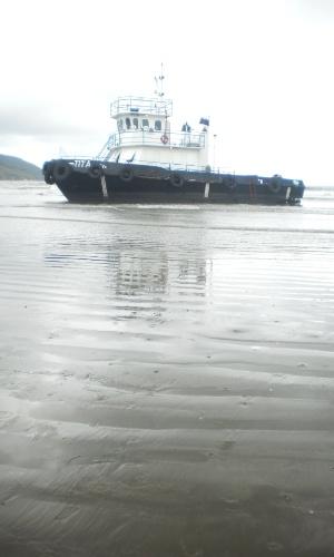 """23.dez.2012 - Rebocador """"Titã"""", que encalhou na praia do Emabré, em Santos (SP), quando tentava fazer o resgate da balsa """"Rubineia"""", encalhada na praia do Boqueirão, a uma distância de cerca de 300 metros"""