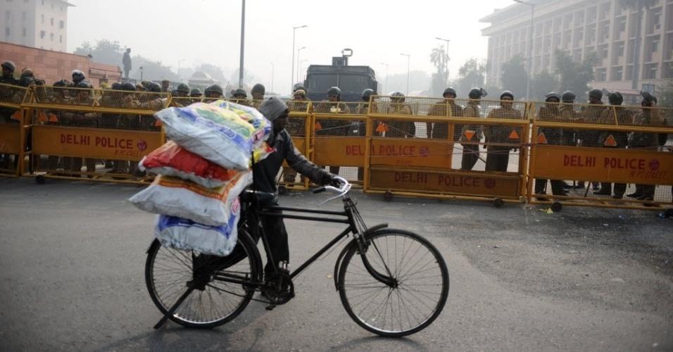 24.dez.2012 - Entregador de bicicleta passa diante de barreira policial no Portão da Índia