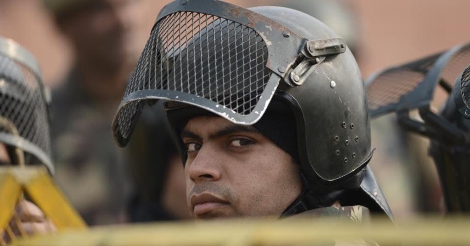 24.dez.2012 - Policiais observam via bloqueada que dá para o Portal da Índia, palco de protestos na última semana