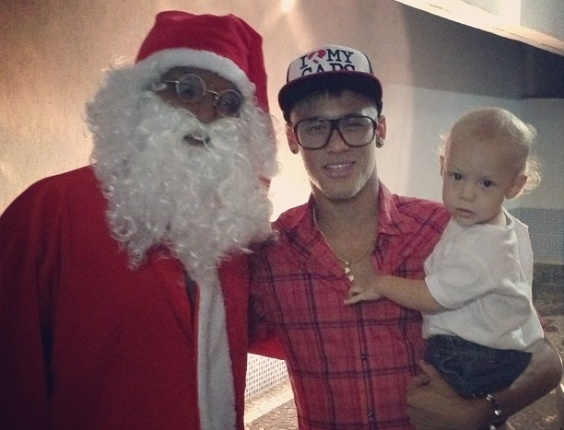 25.dez.2012 - Neymar posa no Natal ao lado do Papai Noel e do filho Davi Lucca