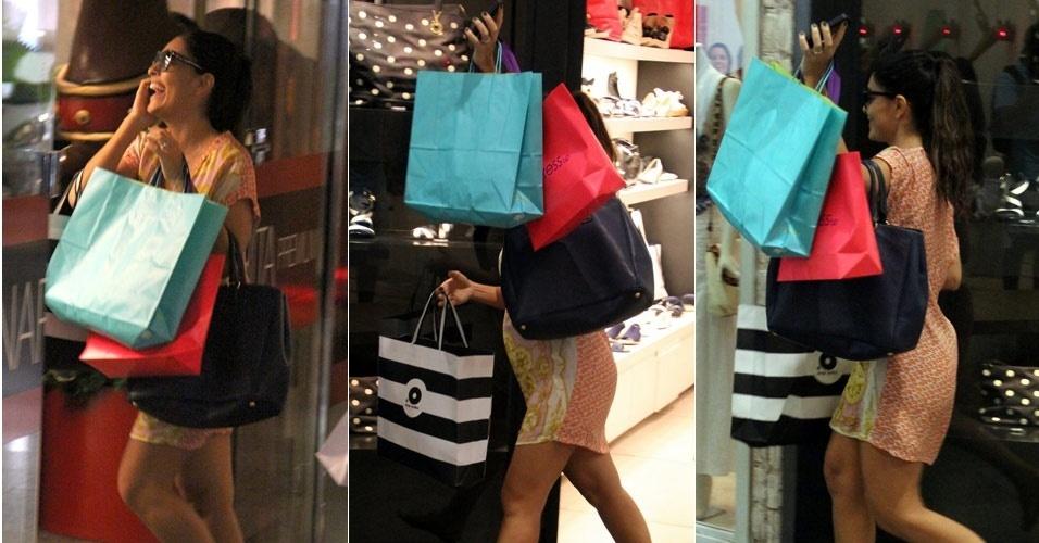 26.dez.2012 - Grávida do segundo filho, a atriz Juliana Paes foi às compras em shopping no Rio e tentou usar sacolas para esconder dos fotógrafos sua barriguinha