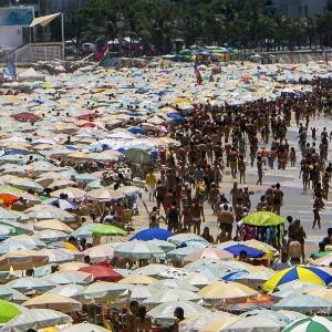 Turistas e cariocas recorrem à praia de Ipanema, no Rio de Janeiro, para se refrescar do calor