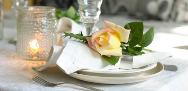 Flores, como rosas, ou frutas decoradas ficam um charme sobre o guardanapo e dão toque festivo à mesa