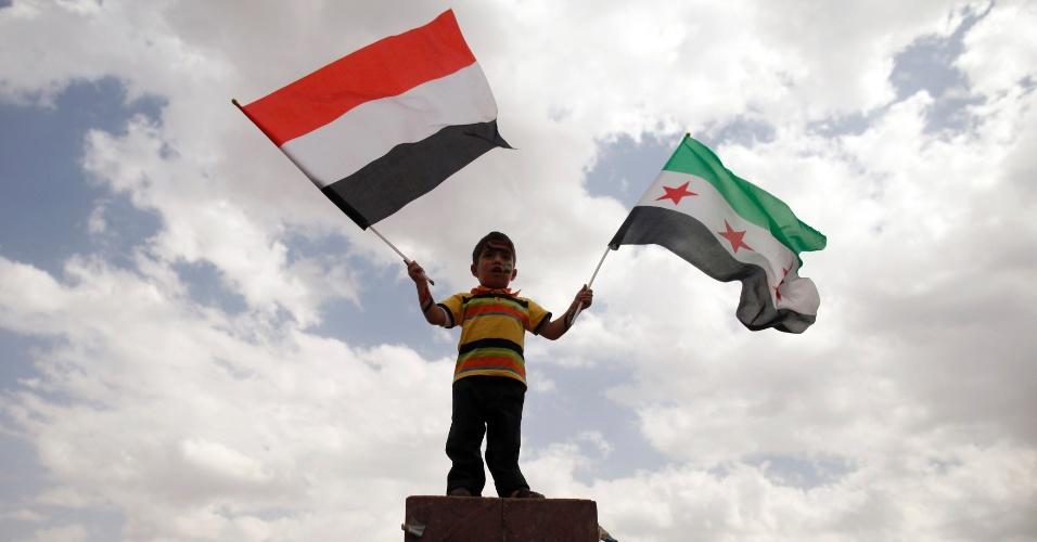 28.dez.2012 - Garoto balança a bandeira iemenita e a bandeira da oposição durante marcha semanal feita por manifestantes pró-democracia na capital Sanaa