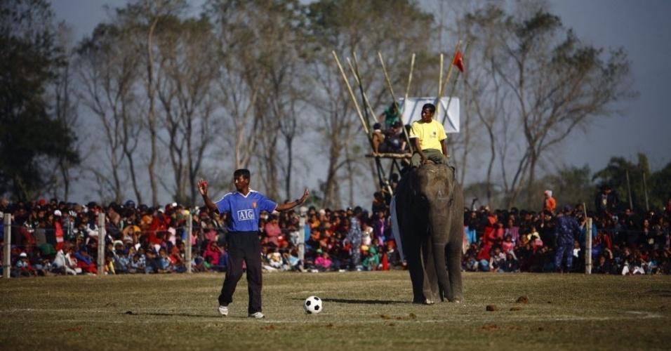 Com camisa falsa do Manchester United, árbitro dá início ao amistoso de futebol ente elefantes no Nepal