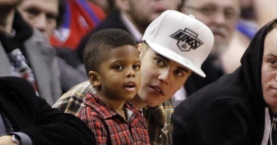 O cantor Justin Bieber cuida do filho do armador Chris Paul, dos Los Angeles Clippers, enquanto assiste ao duelo com os Celtics