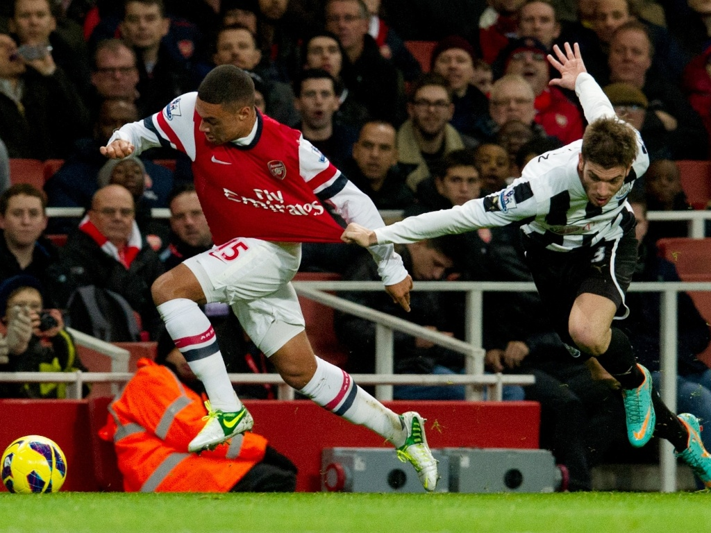 29.dez.2012 -  Alex Oxlade, do Arsenal, tenta se livrar da marcação de Davide Santon, do Newcastle