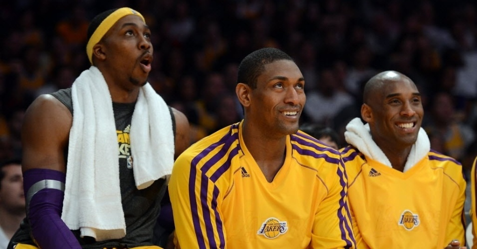 Dwight Howard, Metta World Peace e Kobe Bryant sorriem no banco durante o triunfos dos Lakers sobre o Portland
