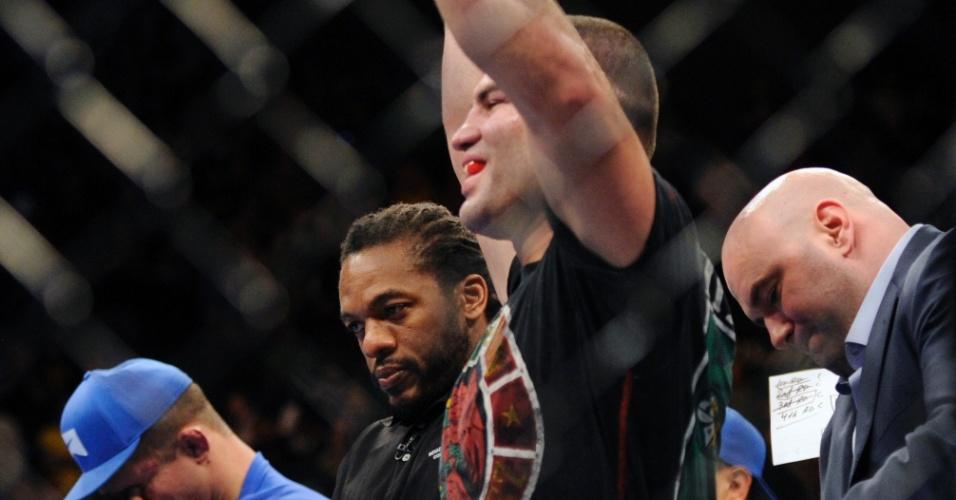 Cain Velásquez (d) comemora ao receber cinturão e brasileiro Junior Cigano lamenta sua derrota ao fundo