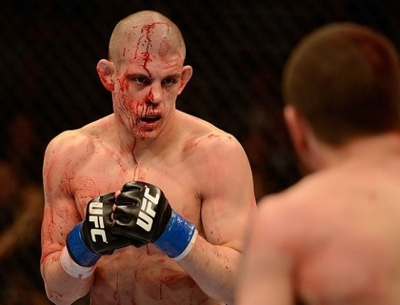 Com a cara cheia de sangue, Joe Lauzon encara Jim Miller durante a luta entre ambos no UFC 155
