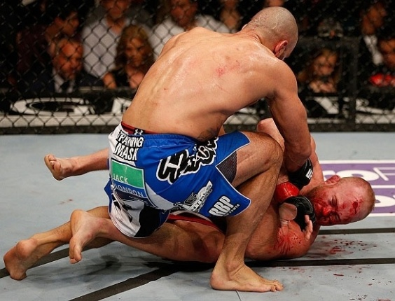 Tim Boetsch sangra no cho enquanto sofre golpes de Costa Philippou no UFC 155