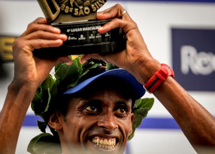 O brasileiro Giovani dos Santos recebe o troféu de 4° colocado da São Silvestre 2012