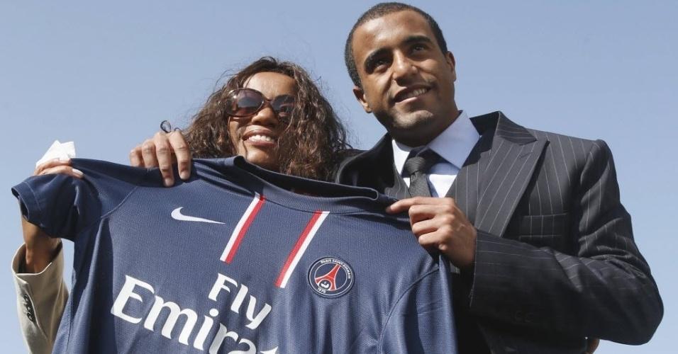01.jan.2013 - Após ser apresentado pelo PSG em Doha, Lucas posa para foto com sua mãe, Fátima, segurando a camisa do clube francês