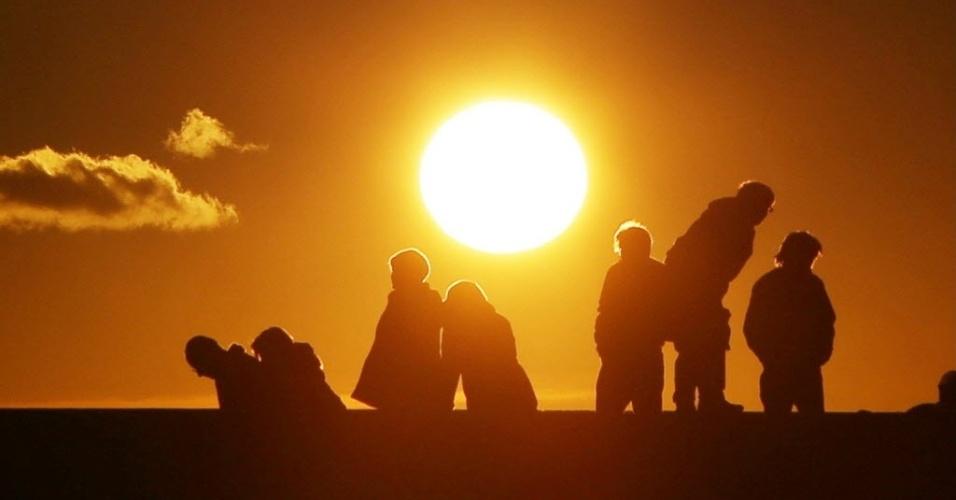 1º.jan.2013 - Pessoas rezam durante o nascer do sol em praia de Minamisoma, em Fukushima (Japão), no primeiro dia do ano. O feriado de Ano Novo dura entre três e quatro dias no país e é o mais importante do ano para os japoneses