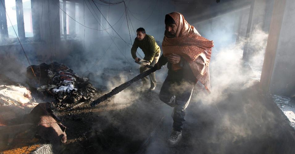 1º.jan.2013- Um civil e um bombeiro tentam retirar pertences de uma casa que pegou fogo em Srinagar, na Índia, nesta terça-feira. Pelo menos uma pessoa ficou ferida. A causa do incêndio ainda não foi esclarecida