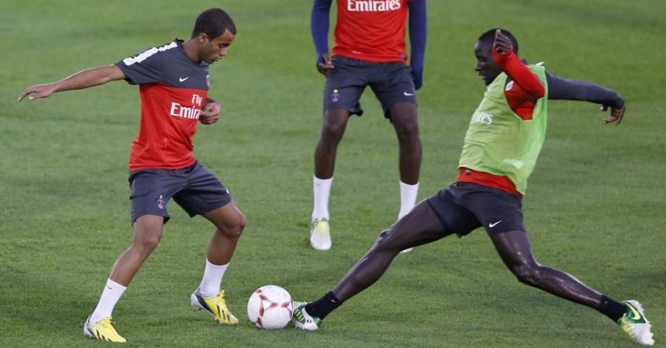 01.jan.2013 - Em seu primeiro treino pelo PSG, no Qatar, meia Lucas (e) disputa bola com Mamadou Sakho