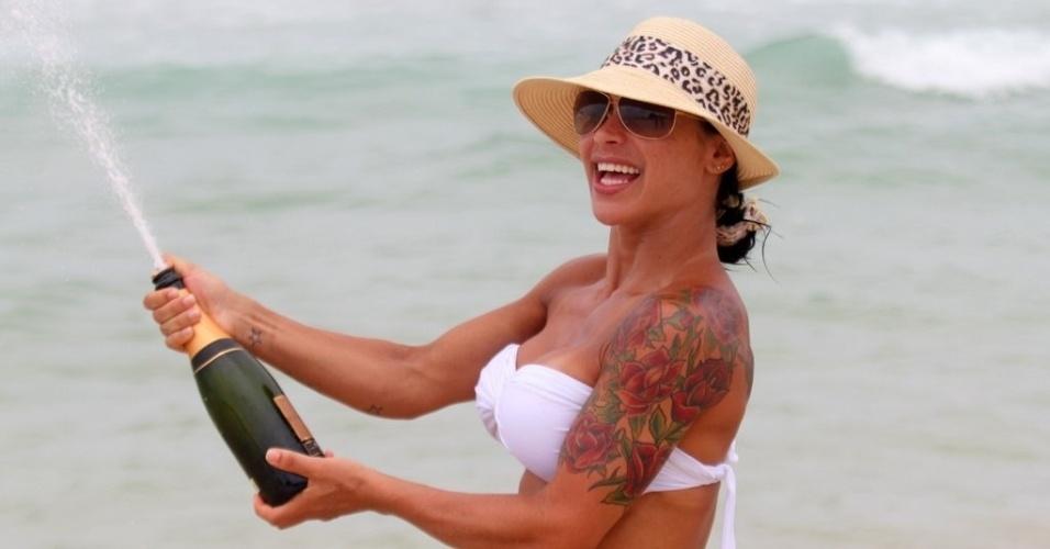 2.jan.2013 Fabiana Frota, mulher de Alexandre Frota, estoura champanhe durante dia de praia em família na Barra da Tijuca