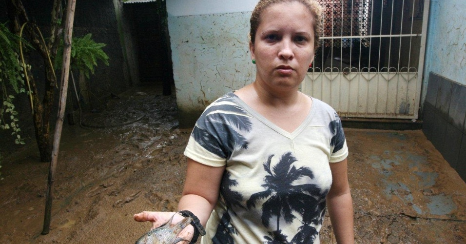03.jan.2012 - Ap&#243;s a enchente, Marcela Gomes Coelho, 32, encontrou um peixe em sua casa no distrito de Xer&#233;m, em Duque de Caxias (SP)
