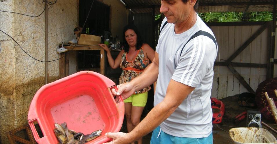 3.jan.2013 - Moradores encontram peixes, após enchente, no bairro de Xerém, em Duque de Caxias (RJ)