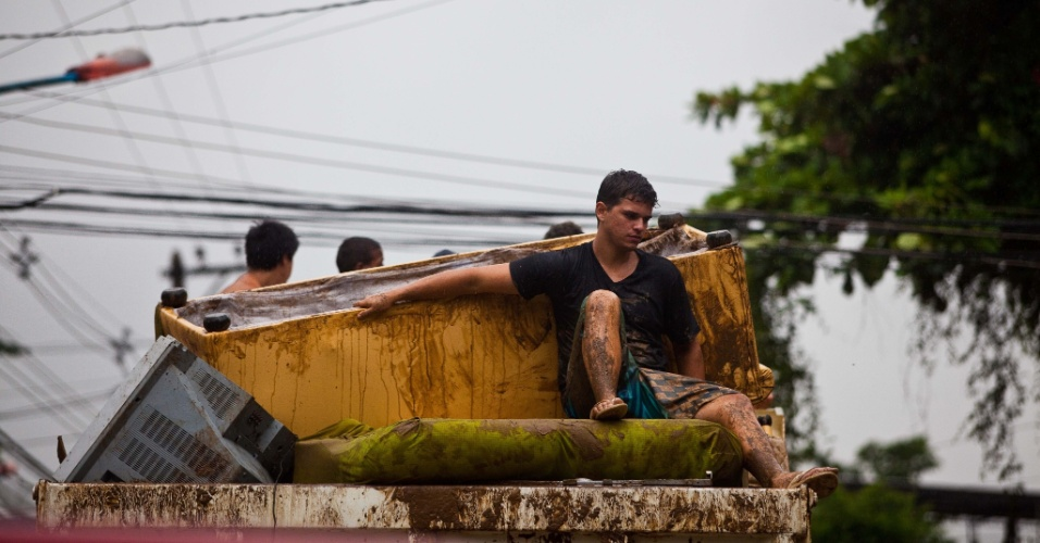 3.jan.2013 - Pessoas saem com pertences em caminhão após  enchente em Xerém, Duque de Caxias (RJ). As fortes chuvas que castigam o estado deixaram um morto e desalojaram 182 pessoas, segundo balanço parcial divulgado pela Defesa Civil estadual
