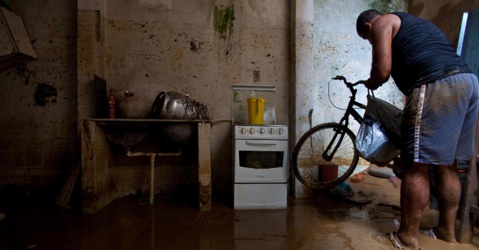 3.jan.2013 - Morador tenta salvar bicicleta, em meio à lama que invadiu sua casa, em Xerém, Duque de Caxias (RJ). Um temporal que caiu durante a madrugada alagou ruas e destruiu casas